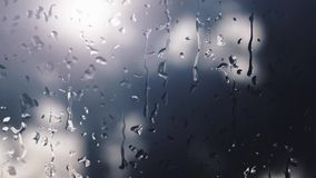 Digitally generated raindrops that fall on a foggy window during the day when it rains and the background is blurred. stock footage