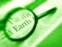 Focus on earth word in news. A concept photograph of the word Earth in the news, focused upon by a magnifying glass.  Green monochrome image. nobody in picture Stock Images