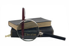 Focus on Education. Magnifying glass focusing on the word education on the back of an ancient book. Isolated image on white Stock Photos