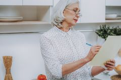Aged gray-haired woman is writing in kitchen royalty free stock image