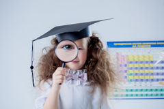 Focus on eye of little girl looking through loupe Royalty Free Stock Photo