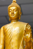 Focus on face of Yellow image of buddha standing. Yellow image of buddha standing Royalty Free Stock Image