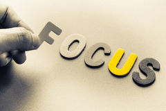 Focus. Finger pick a wood letters of Focus word Stock Image