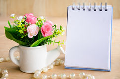 Focus at flower with blank diary binde Stock Photo