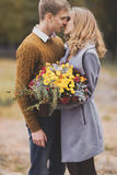Focus on flowers bouquet. Portrait of beautiful young couple hug stock image