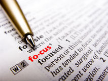 Focus on focus. English dictionary page showing the word focus focused and colored red. The pen is also pointing to the word Stock Photography