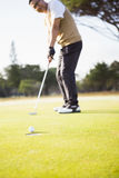 Focus on foreground of golf ball and a hole Stock Images