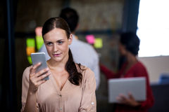 Focus on foreground of woman looking her mobile phone Royalty Free Stock Photography