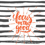 Focus on the good- hand drawn lettering phrase  on the striped grunge background. Fun brush ink inscription for. Photo overlays, greeting card or t-shirt print Royalty Free Stock Photos