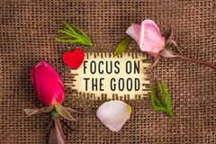 Focus on the good written in hole on the burlap. With rose flowers and wooden red heart royalty free stock image