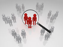 Focus Group. Magnifying glass zeros in on a group of red figures Stock Image