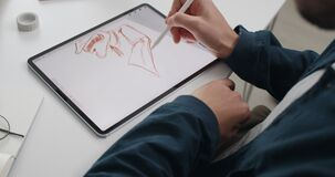 Focus on hands of illustrator using stylus while working on digital tablet. Crop view of artist scetching. Concept of