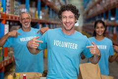 Focus of happy volunteer showing his tee-shirt in front of his team. In a warehouse royalty free stock photo