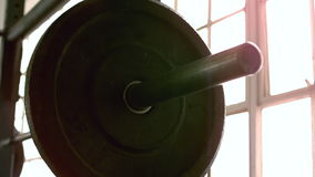 Focus on heavy barbell in crossfit gym. In slow motion stock video footage