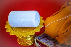 Focus holy thread  roll on gold tray with pedestal. amulet in buddhist religion ceremony. image for objects, background Stock Photography
