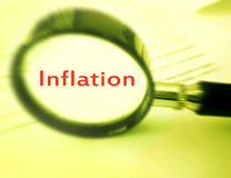 Focus on inflation. A concept photograph of a magnifying glass focused on the word inflaton.  Simple composition with copy space, nobody in picture. Monochrome Stock Photography
