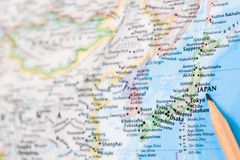 Focus on JAPAN on the world map with pencil pointing.  royalty free stock image