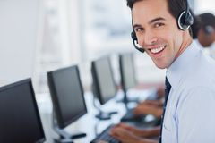 Focus on a joyful call centre agent. With his headset Stock Photography