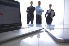 Focus on laptop on the table. Blurred people on stock images