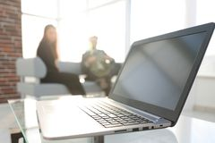 Focus on laptop on the table. Blurred people on background. royalty free stock photos