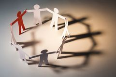 Focus leadership in big cooperate. Circle joining of paper figures with red figure on light background. in concept of business, cooperation and leadership stock photo