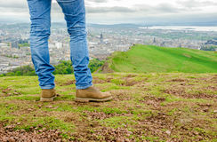 Focus on legs of a female model wearing skinny blue jeans and br. Own suede boots admiring Edinburgh landscape from the top of the Arthur's seat. Scotland, UK Royalty Free Stock Images