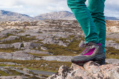 Focus on legs with hiking boots and rocky landscape Royalty Free Stock Photos