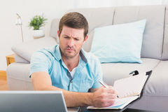 Focus man looking at is laptop and writing on a notebook Royalty Free Stock Photography
