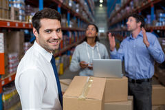 Focus of manager holding cardboard box and smiling in front of workers Stock Photo