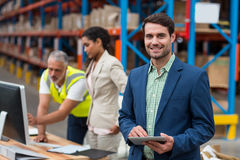 Focus on manager is smiling and holding a tablet in front of his colleagues. In a warehouse royalty free stock image