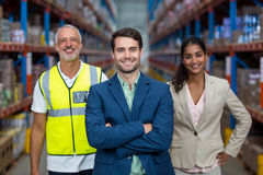 Focus of manager is smiling and posing in front of his colleagues. In a warehouse stock photos