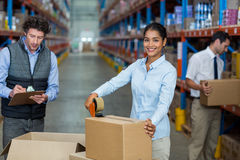 Focus of manager is smiling and posing during work with his colleagues. In a warehouse stock photos