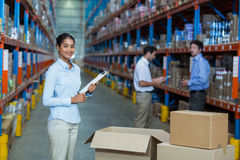 Focus of manager is smiling and posing during work. In a warehouse stock images