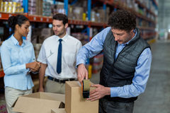 Focus of manager is working in front of his colleagues. In a warehouse royalty free stock photography