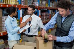 Focus of managers are talking in the middle of cardboard boxes. In a warehouse royalty free stock images