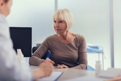 Attentive woman is receiving doctor recommendation in the hospital stock images