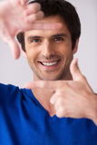 Focus on me!. Handsome young man in blue sweater gesturing finger frame and smiling while standing against grey background Stock Photo