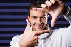 Focus on me!. Playful young man in white sweater gesturing finger frame and smiling while standing against striped background Stock Photo