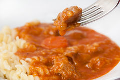 Focus on the meat on the fork over goulash with macaroni Stock Photos