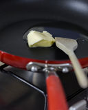 Focus on melting butter on hot hard anodized skillet with wooden Royalty Free Stock Photography