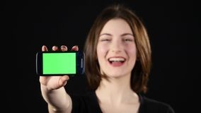 Focus on mobile phone. Young woman hands showing blank smartphone screen  on green background and pointing on Stock Image