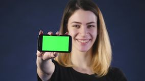 Focus on mobile phone. Young woman hands showing blank smartphone screen isolated on green background and pointing on stock video