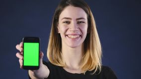 Focus on mobile phone. Young woman hands showing blank smartphone screen isolated on green background and pointing on