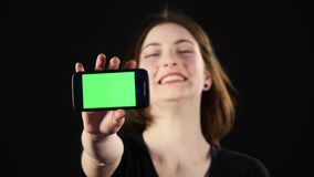 Focus on mobile phone. Young woman hands showing blank smartphone screen isolated on green background and pointing on Royalty Free Stock Photos