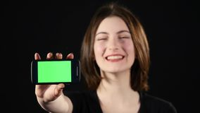 Focus on mobile phone. Young woman hands showing blank smartphone screen isolated on green background and pointing on Stock Image