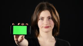 Focus on mobile phone. Young woman hands showing blank smartphone screen isolated on green background and pointing on Stock Images