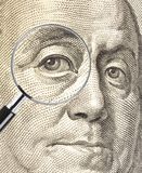 Focus on money. Ben Franklin dollar image with eye enlarged by a magnifying glass Royalty Free Stock Photography