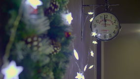 Focus moving from Christmas wreath to clock showing twelve o`clock stock footage