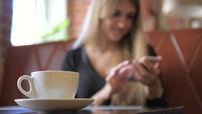Focus on the mug, a woman using a smartphone in the background is blurred. Young blond woman sitting on a sofa in a cafe. Focus on the white cup which stands in stock footage