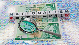 Focus on nationalism. Text ' nationalism' in uppercase letters inscribed on small white cubes with hand magnifier to demonstrate focus on subject, pound notes in royalty free stock images